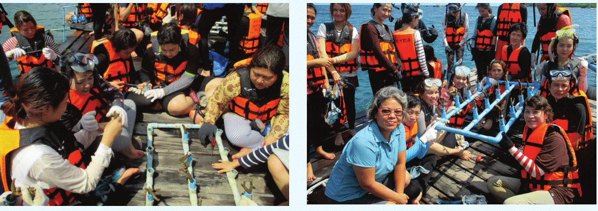 People in life jackets holding up pvc pipes containing young coral for transplant
