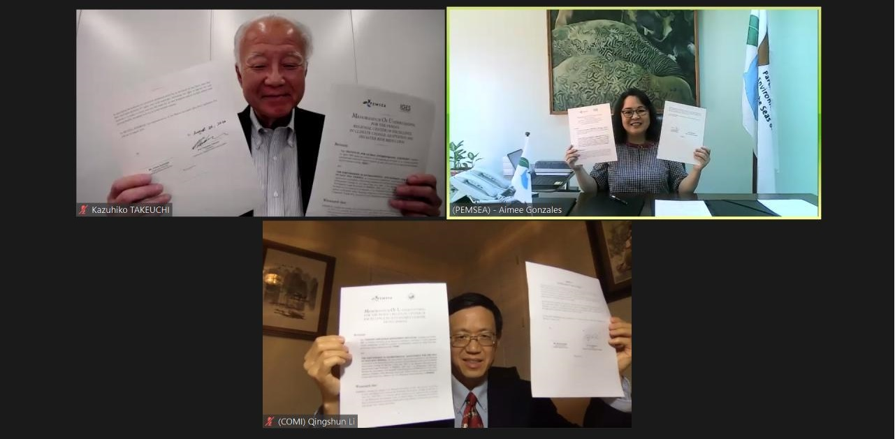 Representatives of COMI hold up their signed papers along with the PEMSEA Executive Director