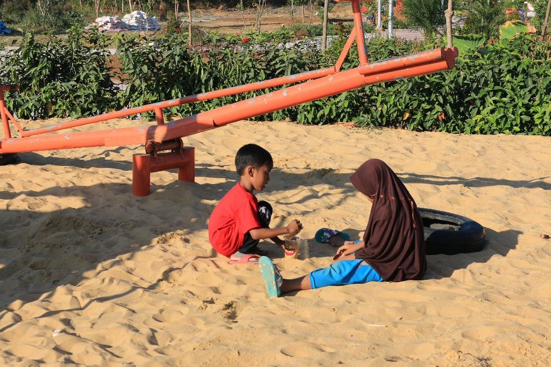 Two children playing on the sand next to a see-saw